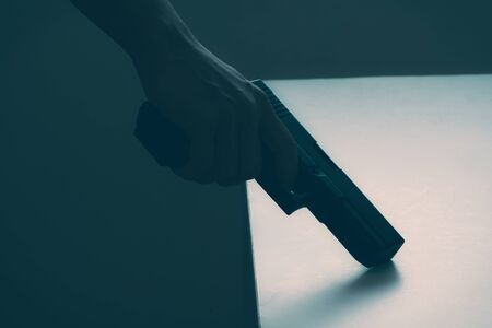 Hand of man with gun, monotone image