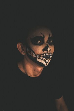 Man with skull face makeup on black background, portrait photography