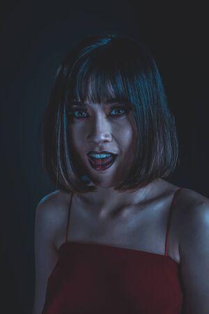 Weird woman with dark tone makeup on black background, portrait photograph Reklamní fotografie