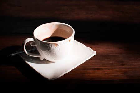 Cup of coffee on brown wooden table with morning light