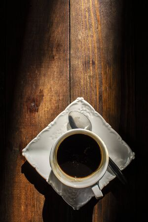 Cup of coffee on brown wooden table with sunlight
