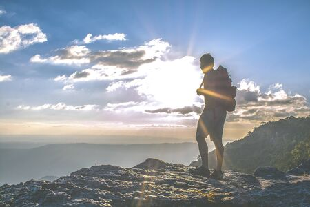 Man with backpack standing on cliff at sunset time, sun rays on background with clouds, this man looking at view,  warm tone and almost in silhouette photo Reklamní fotografie