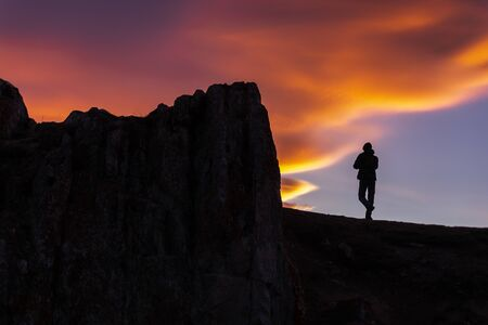 Silhouette photography of person on cliff at twilight, beautiful color shades of sky in the evening