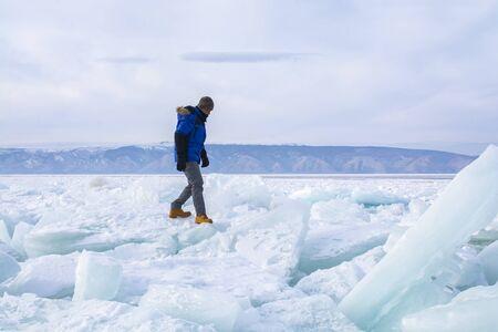 Man walking on broken ice in Lake Baikal, Russia, landscape photography