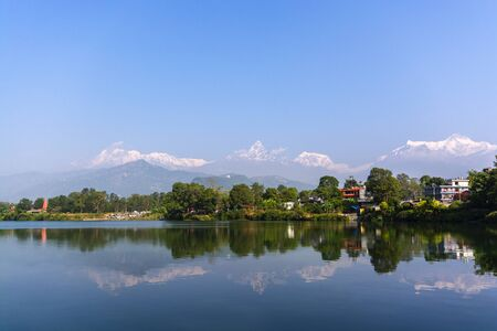 Reflection of mountains in lake against blue sky, Phewa Lake, Nepal