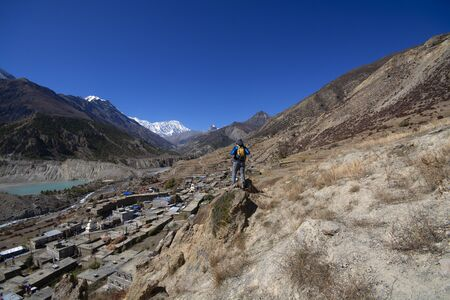 Trekker on cliff looking at view of mountain, Annapurna Conservation Area, Nepal