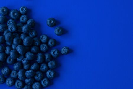 Blueberries on blue paper background, dark blue tones image with space for text Stock Photo