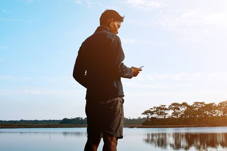 Man standing and using smartphone near lake at twilight