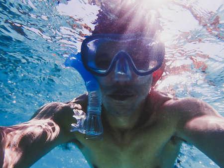 Man doing underwater selfie photography, water sport activity