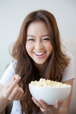 Young beautiful women holding a bowl of popcorn