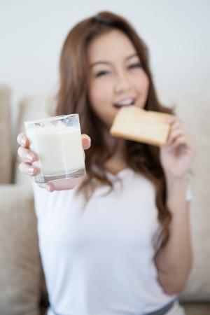 블러 어린 소녀는 우유 한 잔을 들고 신선한 토스트를 먹고있다