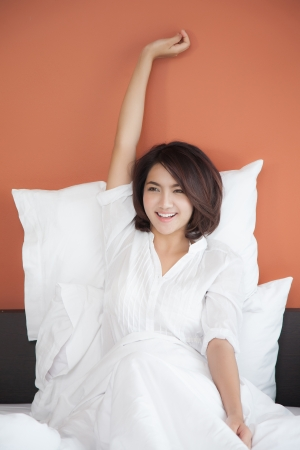 awaken: Young women waking up stretching in the morning on bed with happy smile face