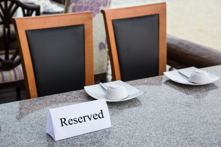 Reserved sign on restaurant table with chair photo