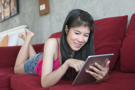 Young beautiful woman using computer tablet on red sofa photo
