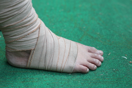 articulation: Foot and Ankle injured with bandage on green background Stock Photo