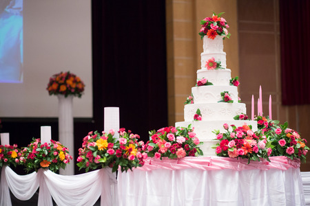 c�r�monie mariage: Belle g�teau d�corer avec des fleurs rose et de bougies pour la c�r�monie de mariage