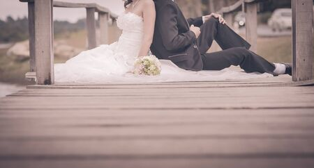 elegant dress: wedding couple sit on bridge with space. Cross processed for vintage look