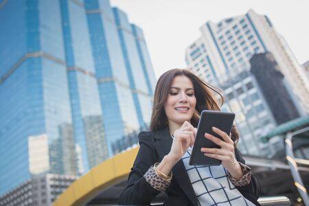 confident business woman: Portrait of successful smart business woman looking confident and smiling holding tablet computer