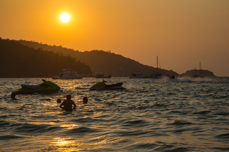 moto acuatica: Sunset time with people play jet ski and Sailing Yacht on sea Foto de archivo
