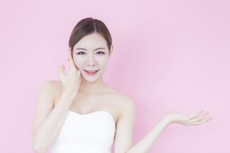 완벽 한 피부를 가진 젊은 아름 다운 아시아 여자의 초상화. 분홍색 배경에 제품을 제시하는 빈 복사본 공간을 보여주는 미소 소녀