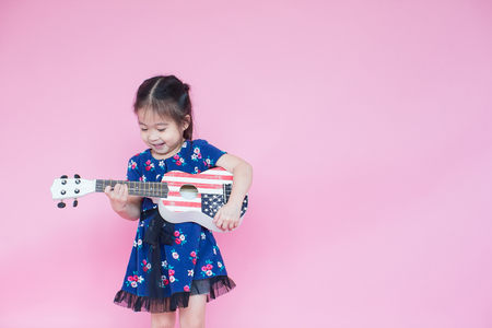 Little beautiful asian girl playing guitar on pink background with copy space