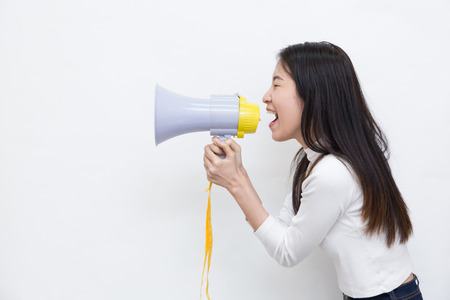 Young Asian woman shouting and screaming with the megaphone on white background with copy space Stock Photo