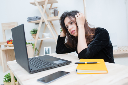 Beautiful smiling Asian student woman learning from online education service, Young Asian woman looking computer laptop confuse about her business work