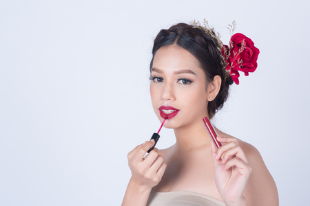 sexy asian woman: Asian beautiful smile woman with clean fresh skin for skincare or healthy and make up concept holding red lipstick on white background with copy space for product and design