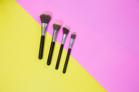 Top view of Make up cosmetics and brushes products on colorful background with copy space