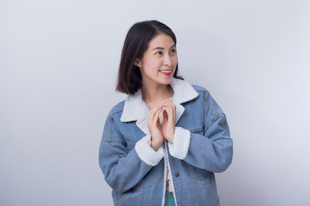 Caucasian smiling excited woman showing her hand with expression feeling surprised and amazed,  Positive happy young asian girl wearing blue casual clothes portrait in studio 版權商用圖片