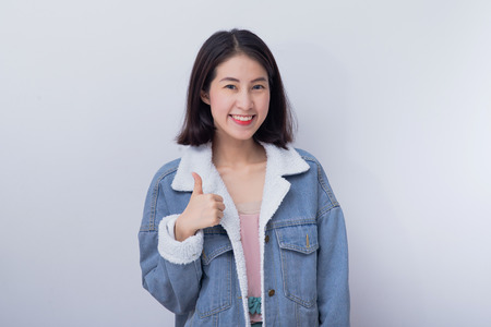 Caucasian smiling woman showing her hand thumbs up in concept good job,  Positive happy young asian girl wearing blue casual clothes portrait in studio 版權商用圖片