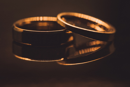 Close up of Diamond wedding rings on gold background with copy space and selective focus 版權商用圖片