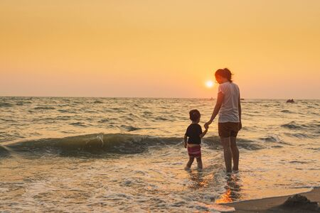 Smiling cute girl and mother stand on the beach with sunset at background, Happy family vacation concept 스톡 콘텐츠