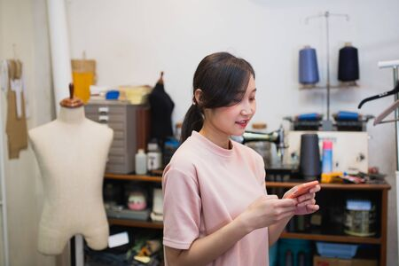 Young Asian tailor check order from mobile phone 스톡 콘텐츠
