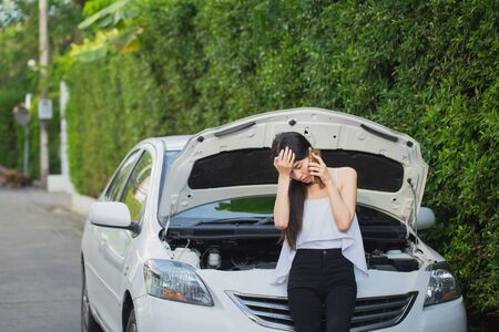 Asian stressed woman near a car breakdown using mobile phone feeling desperate for trouble with vehicle 스톡 콘텐츠