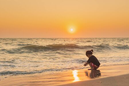 Smiling cute girl playing on the beach with sunset at background, Happy family vacation concept
