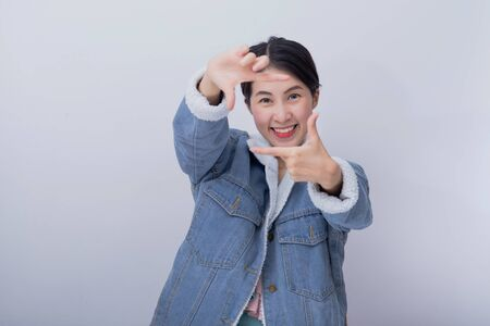 Young asian smiling excited woman showing her hand with expression feeling surprised and amazed,  Positive happy caucasian girl wearing blue casual clothes portrait in studio