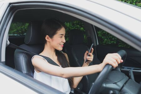 Asian stressed woman near a car breakdown using mobile phone looking for help