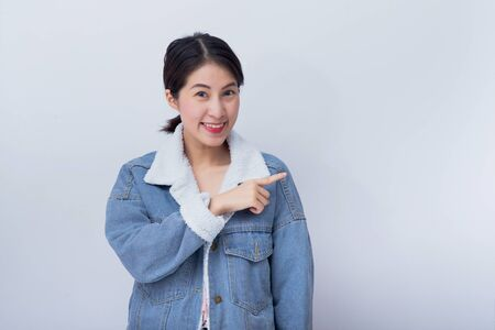 Young Caucasian Asian smiling woman pointing on white copy space background for product, business and advertise concept 스톡 콘텐츠