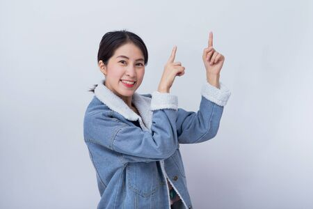 Portrait of happy young asian lady pointing on white copy space background for product, business and advertise concept