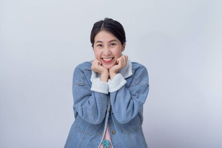 Smiling Asian woman feeling happy on white background with copy space