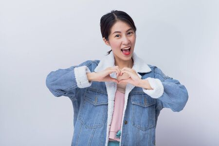 Caucasian smiling woman showing her hand with heart sign,  Positive happy young asian girl wearing blue casual clothes portrait in studio 스톡 콘텐츠