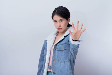 Caucasian smiling women showing hand stop, Bad Emotion young asian girl wearing blue casual clothes portrait in studio
