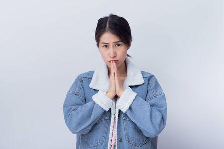 Kaukasische lächelnde Frauen, die ihre Hand zeigen Respektieren, positives glückliches junges asiatisches Mädchen, das blaues Freizeitkleidungsporträt im Studio trägt