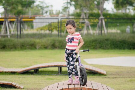 Little Asian child girl ride bike at playground Banco de Imagens