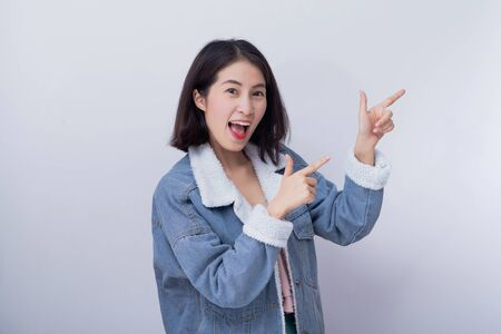 Caucasian smiling woman point her hand at background space for profuct, Positive happy young asian girl wearing blue casual clothes portrait in studio