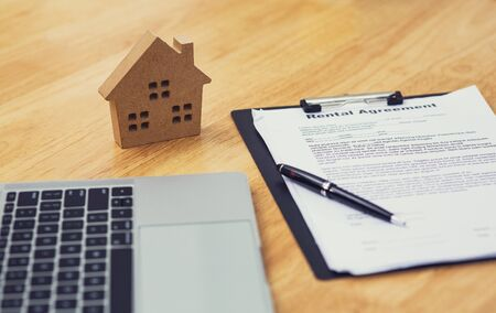 Home model put near Lease or Rental agreement document and laptop with copy space, real estate Business for buy , loan or investment concept