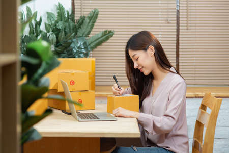 Asian woman using laptop writting on package box working at home office for online marketing delivery small business owner