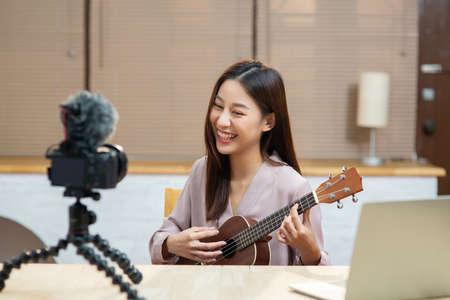 Asian teenage girl look at camera filming her self and playing ukulele guitar Reklamní fotografie