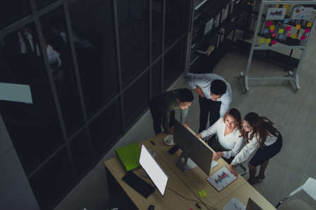 Group of diversity business people working late in office at night. Two Caucasian men and Asian girl feel happy and success for new business. Working late night and overtime concept